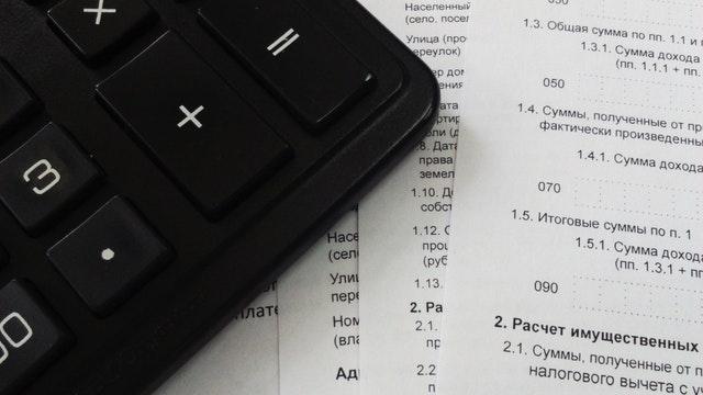 Kalkulačka a vedle ní papíry s ruským textem